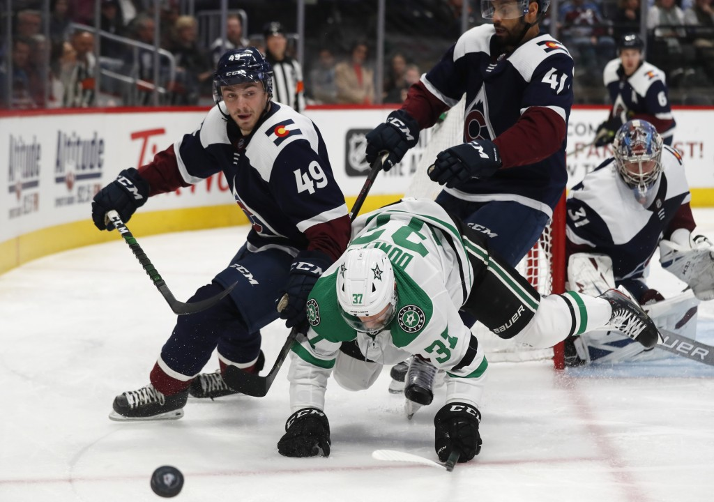 Dallas Stars center Justin Dowling, center, tumbles to the ice while pursuing the puck betwen Colorado Avalanche defenseman Samuel Girard, left, and c...
