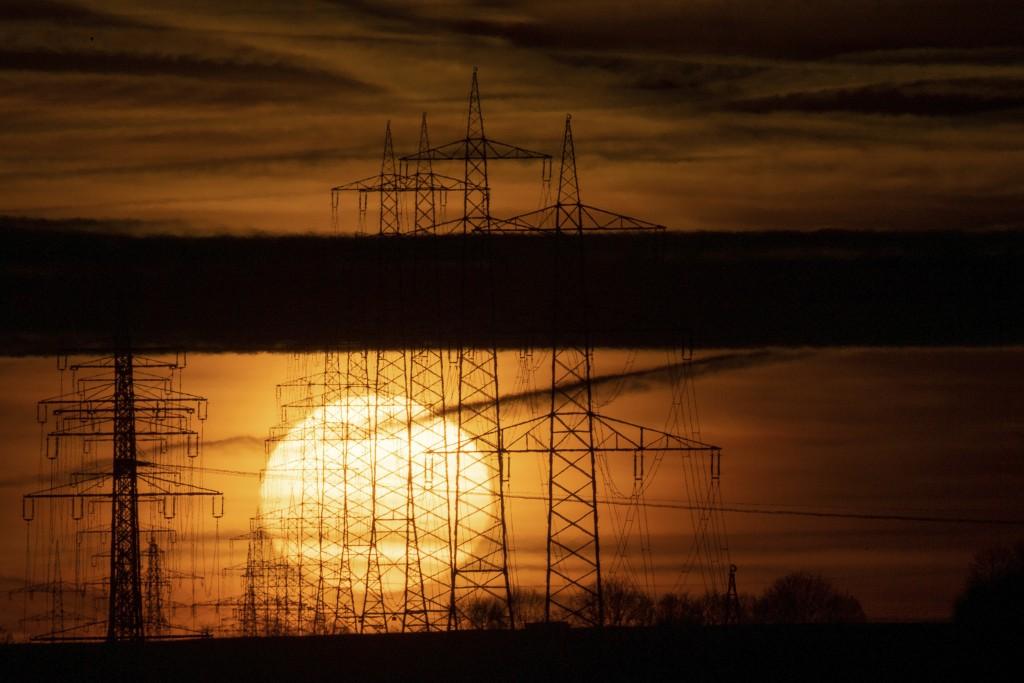 The sun rises behind high voltage pylons near Schwieberding, Germany, Wednesday,  Jan. 15, 2020 (Sebastian Gollnow/dpa