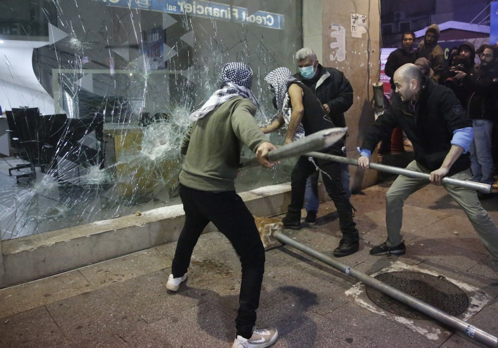 Anti-government protesters smash a bank widow, during ongoing protests against the Lebanese central bank's governor and against the deepening financia...
