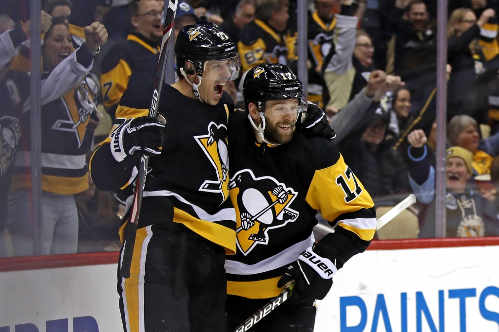 Pittsburgh Penguins' Bryan Rust (17) celebrates his goal with Evgeni Malkin (71), who had an assist, during the second period of the team's NHL hockey...