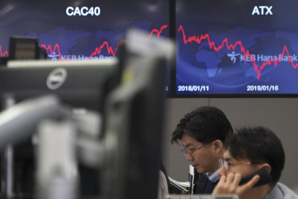 A currency trader talks on the phone at the foreign exchange dealing room in Seoul, South Korea, Wednesday, Jan. 15, 2020. Asian shares have retreated...