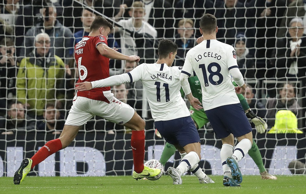 Tottenham's Erik Lamela, centre, shoots to score his side's second goal during the English FA Cup third round replay soccer match between Tottenham Ho...