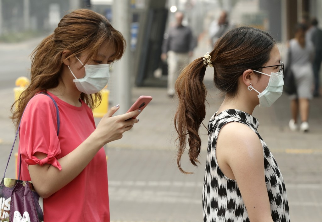 FILE - In this Jan. 2, 2020, file photo, pedestrians wear masks as smoke shrouds the Australian capital of Canberra, Australia. It's an unprecedented ...