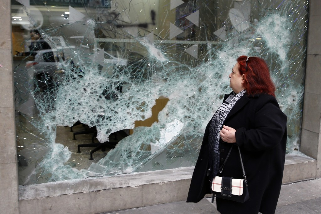 A woman looks at the broken glass of Bank of Beirut that was smashed by anti-government protesters in Beirut, Lebanon, Wednesday, Jan. 15, 2020. Banks...