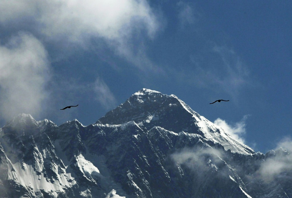 FILE - In this May 27, 2019, file photo, birds fly as Mount Everest is seen from Namche Bajar, Solukhumbu district, Nepal. Five climbers are attemptin...