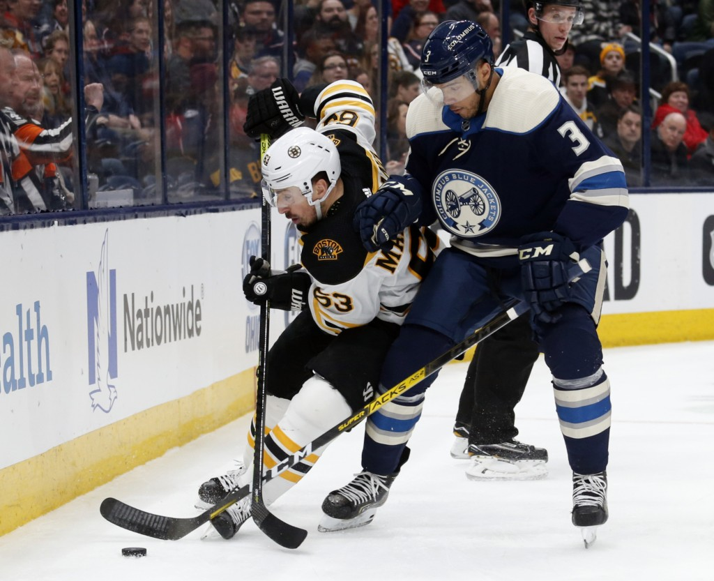 Boston Bruins forward Brad Marchand, left, tries to control the puck next to Columbus Blue Jackets defenseman Seth Jones during the first period  of a...