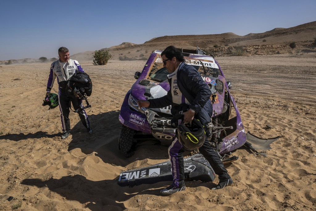In this Tuesday, Jan. 14, 2020 photo, driver Peter Van Merksteijn, of Netherlands, foreground, and co-driver Michael Orr, of Great Britain, after cras...