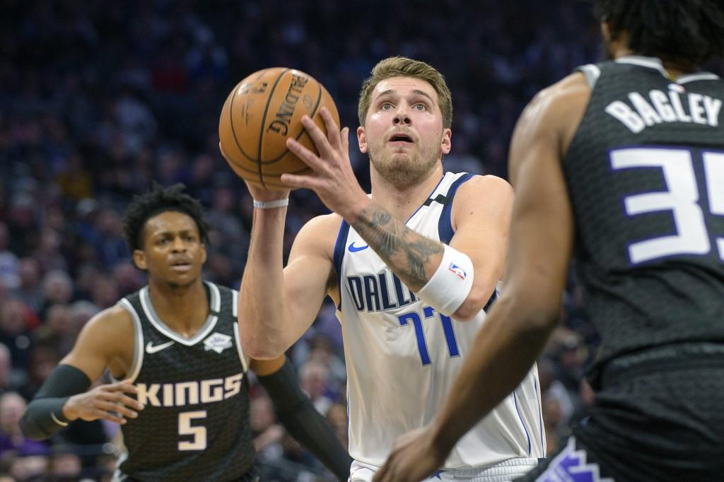 Dallas Mavericks forward Luka Doncic (77) drives to the basket past Sacramento Kings guard De'Aaron Fox (5) and forward Marvin Bagley III (35) during ...