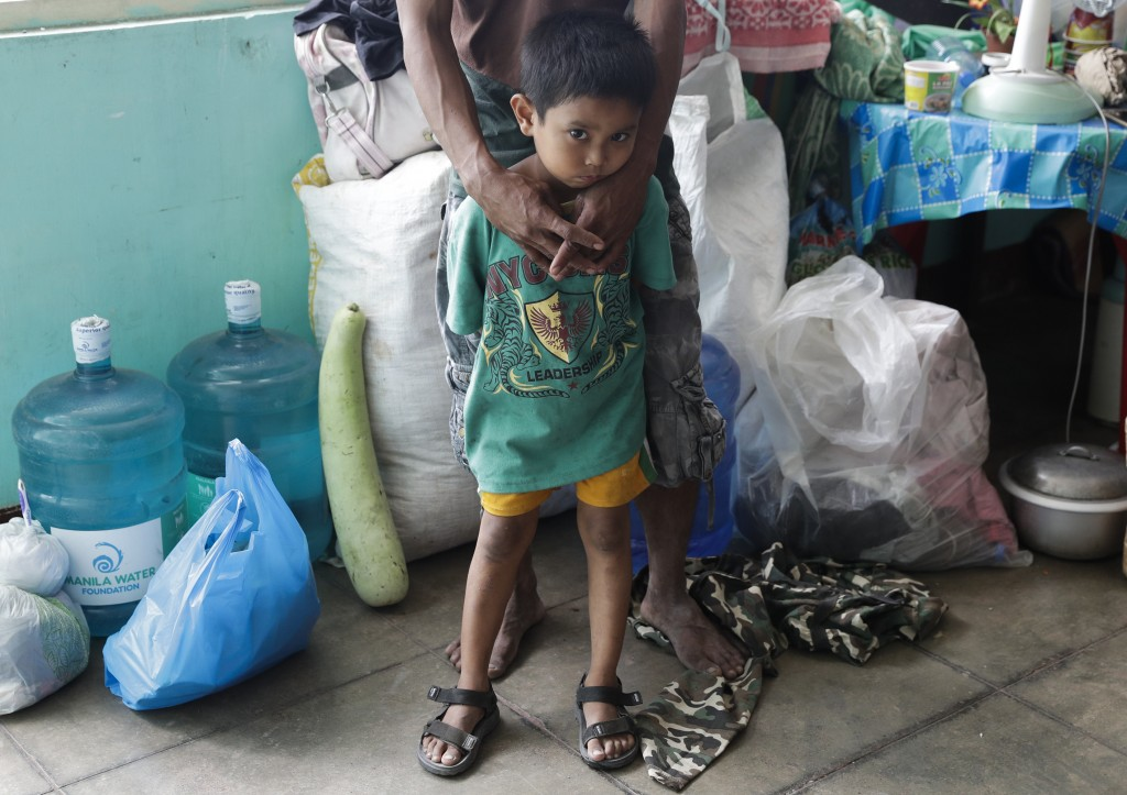 A boy waits with his father inside an evacuation center in Santa Teresita, Batangas province, southern Philippines on Thursday Jan. 16, 2020. Taal vol...