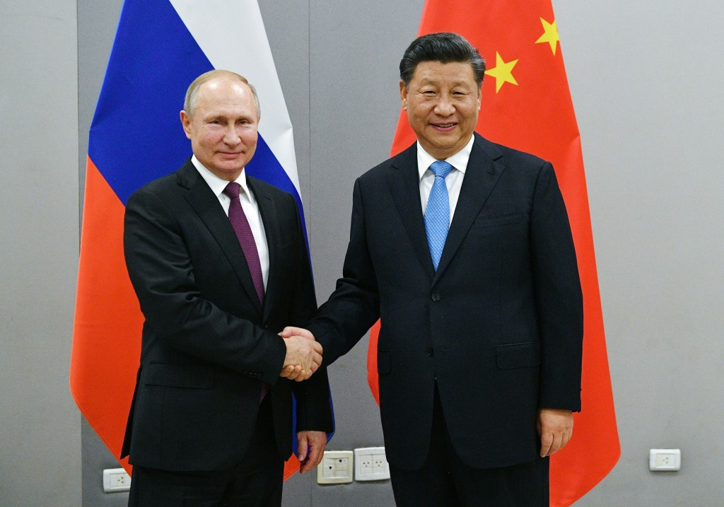 FILE - In this Nov. 12, 2019, file photo, Russian President Vladimir Putin, left, and China's President Xi Jinping shake hands prior to their talks on...