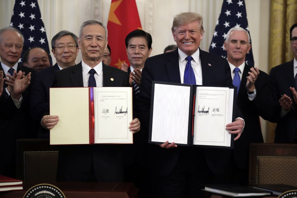 President Donald Trump signs a trade agreement with Chinese Vice Premier Liu He, in the East Room of the White House, Wednesday, Jan. 15, 2020, in Was...