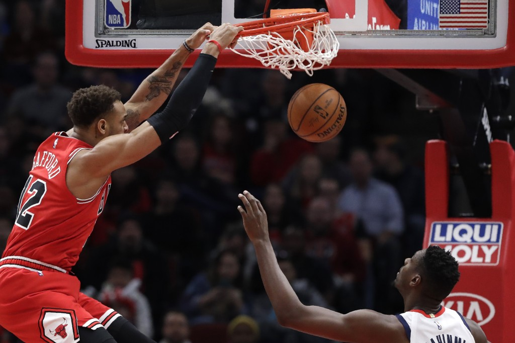 Chicago Bulls forward Daniel Gafford, left, dunks as Washington Wizards center Ian Mahinmi watches during the first half of an NBA basketball game in ...