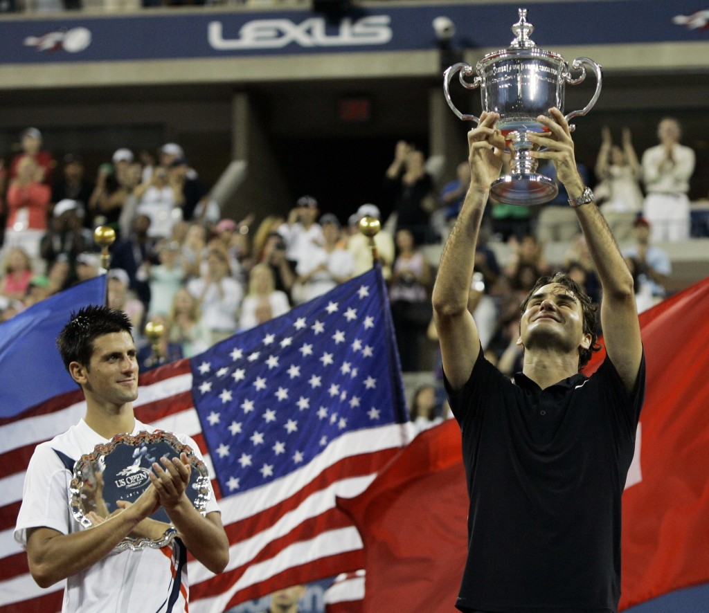 FILE - In this Sept. 9, 2007, file photo, Novak Djokovic, left, of Serbia applauds as Roger Federer of Switzerland holds up the championship trophy af...