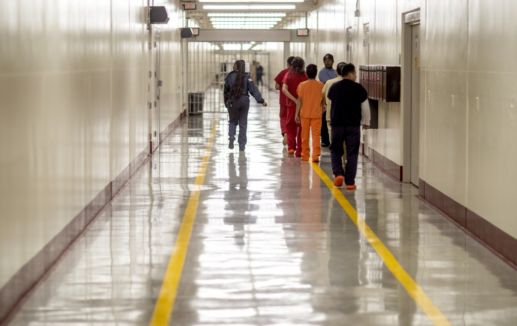 In this Nov. 15, 2019, photo, detainees walk through the halls at the Stewart Detention Center, in Lumpkin, Ga. The rural town is about 140 miles sout...