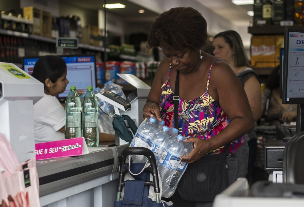 Marcia Helena buys bottled water at a supermarket in the Copacabana neighborhood of Rio de Janeiro, Brazil, Jan. 15, 2020. There's a creeping sense of...