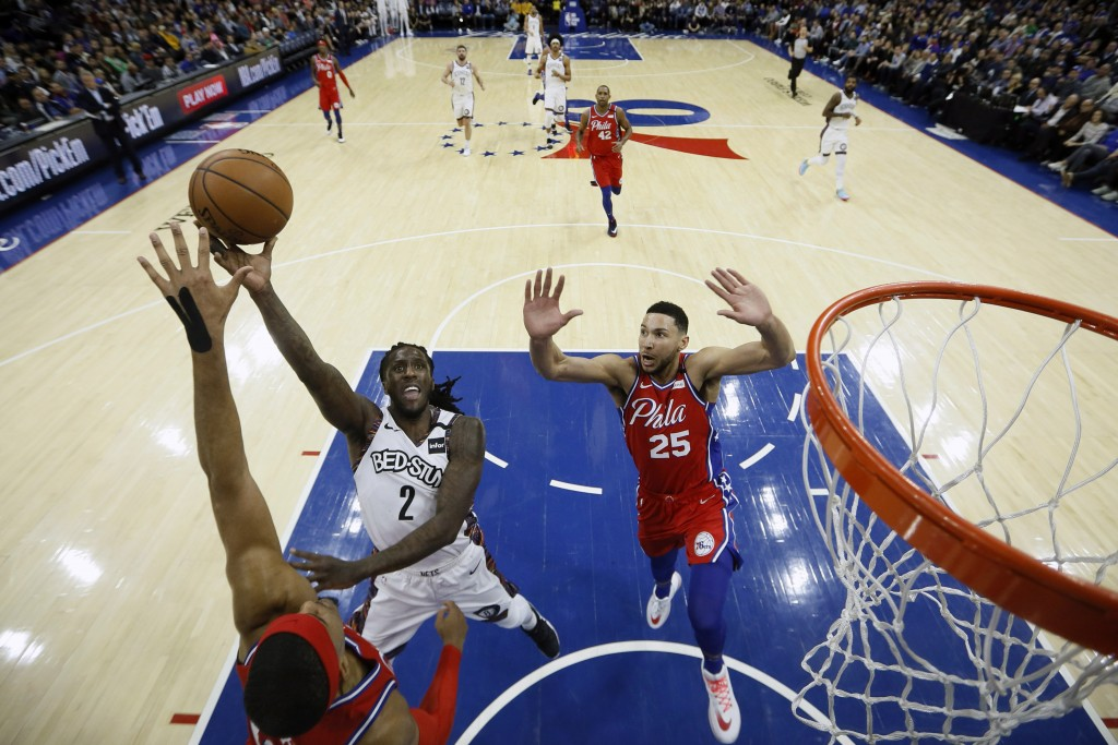 Brooklyn Nets' Taurean Prince, center, goes up for a shot between Philadelphia 76ers' Tobias Harris, left, and Ben Simmons during the first half of an...