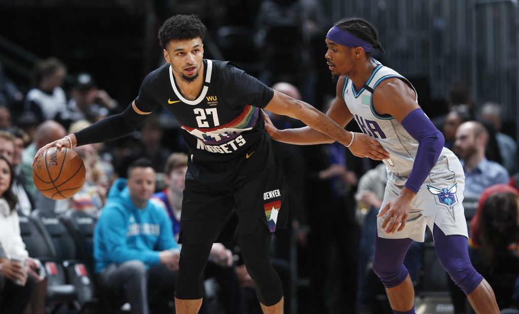 Denver Nuggets guard Jamal Murray, left, keeps Charlotte Hornets guard Devonte' Graham at bay during the first half of an NBA basketball game Wednesda...