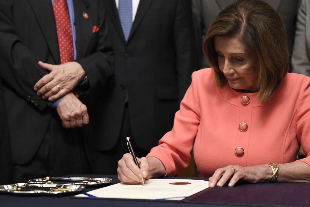 House Speaker Nancy Pelosi of Calif., signs the resolution to transmit the two articles of impeachment against President Donald Trump to the Senate fo...