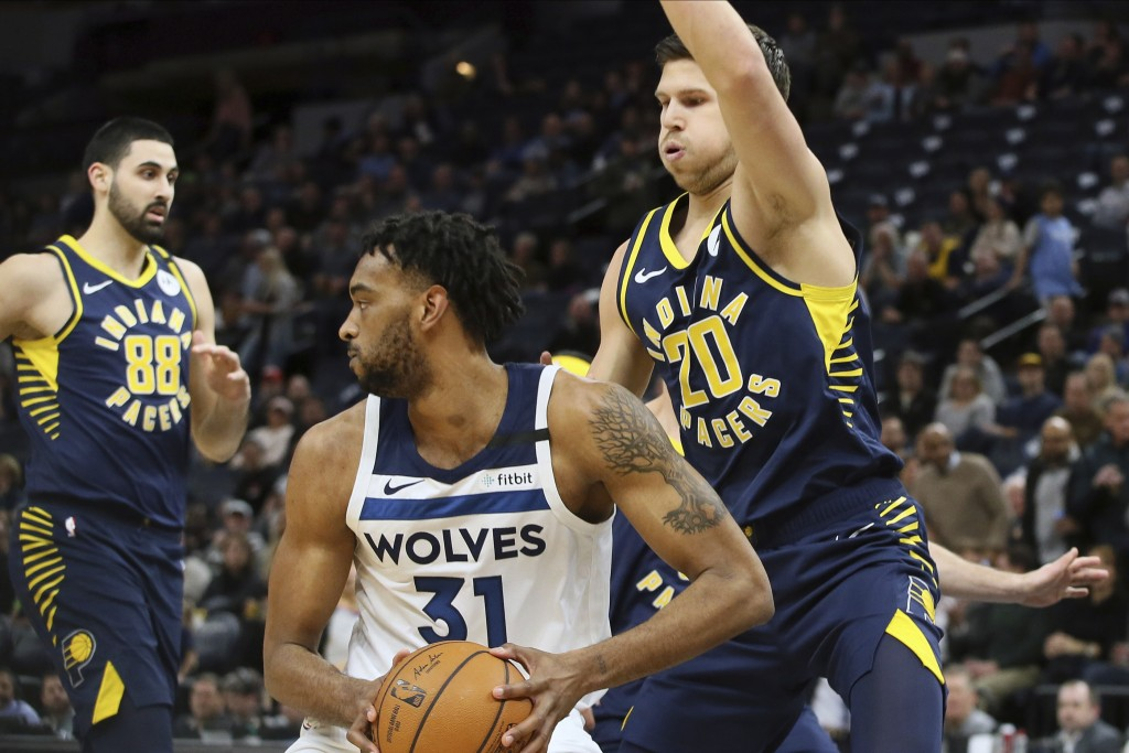 Minnesota Timberwolves' Keita Bates-Diop, center, looks for help as Indiana Pacers' Doug McDermott, right, looms over him in the first half of an NBA ...