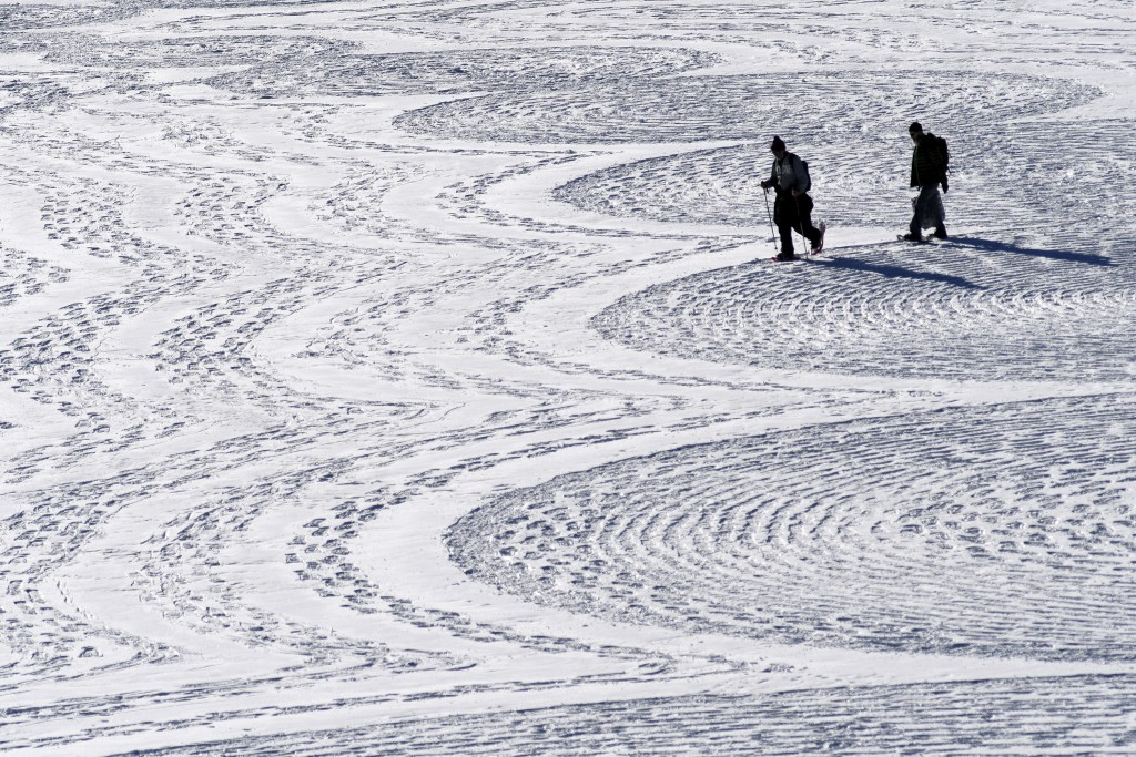 In this photo taken Jan. 7, 2020, British artist Simon Beck, left, and a volunteer put the final touches on a geometrical snow drawing on a frozen res...