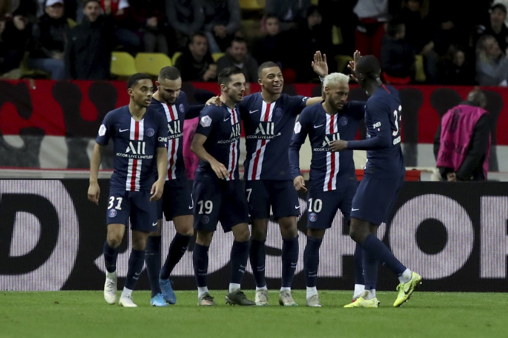 PSG's Kylian Mbappe, center, celebrates with teammates after scoring his side's fourth goal during the French League One soccer match between Monaco a...