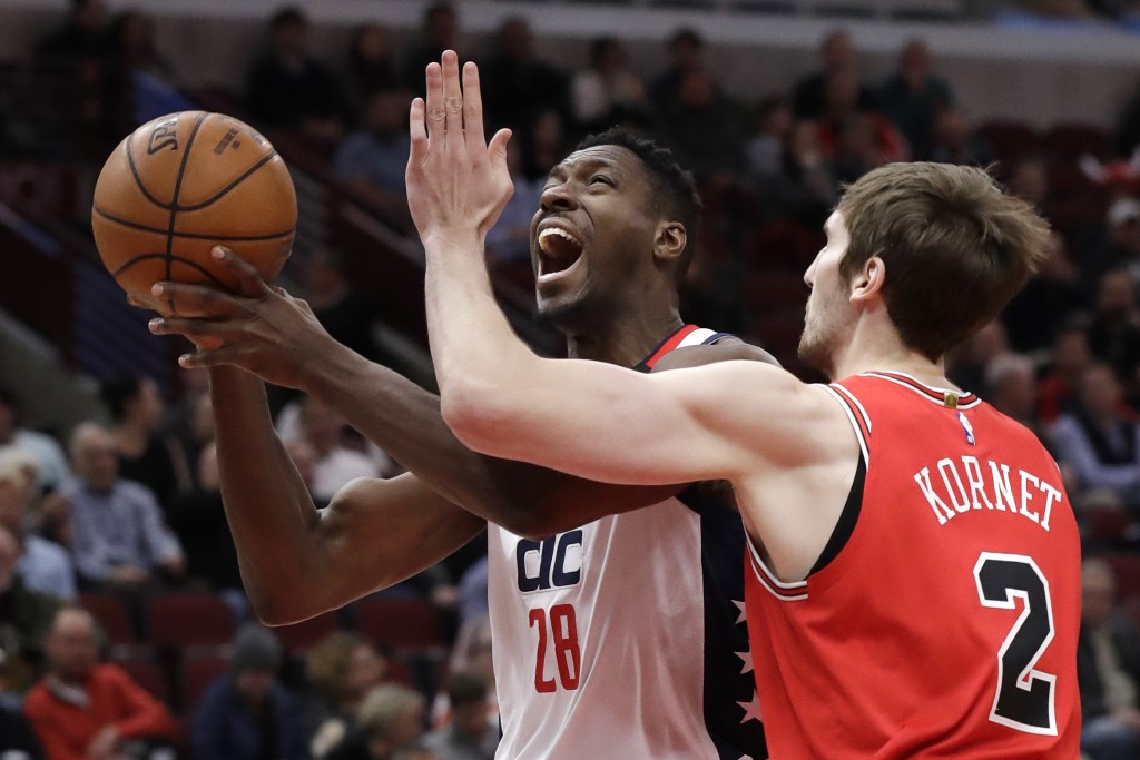 Washington Wizards center Ian Mahinmi, left, drives to the basket as Chicago Bulls forward Luke Kornet defends during the first half of an NBA basketb...