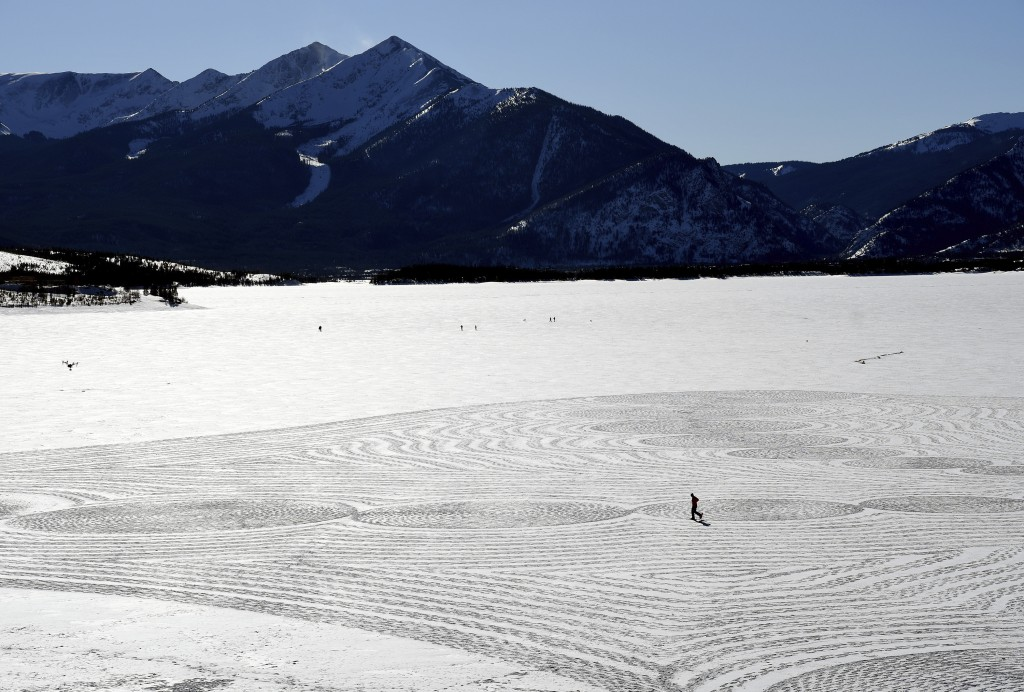 In this photo taken Jan. 7, 2020, British artist Simon Beck uses snowshoes to create a massive geometrical design on a frozen reservoir near Silvertho...