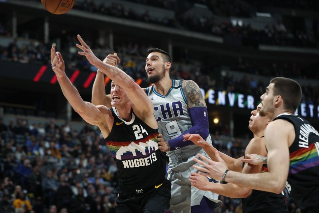 Denver Nuggets forward Mason Plumlee reaches for a rebound near Charlotte Hornets center Willy Hernangomez (9) and Nuggets forward Juan Hernangomez, r...