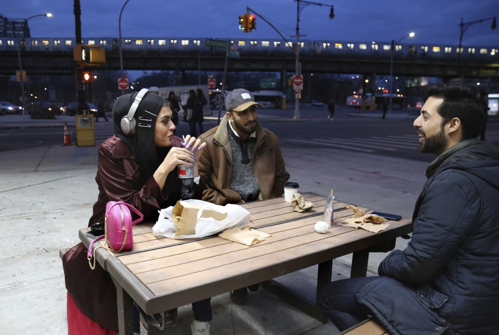 In this Dec. 27, 2019, photo, Amani Al-Khatahtbeh, founder of MuslimGirl.com, left, sips a soda while talking with old friends Mohammed Ali, right, an...