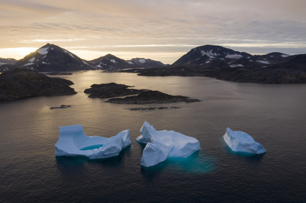 FILE - In this Aug. 16, 2019, file photo, large icebergs float away as the sun rises near Kulusuk, Greenland. The decade that just ended was by far th...