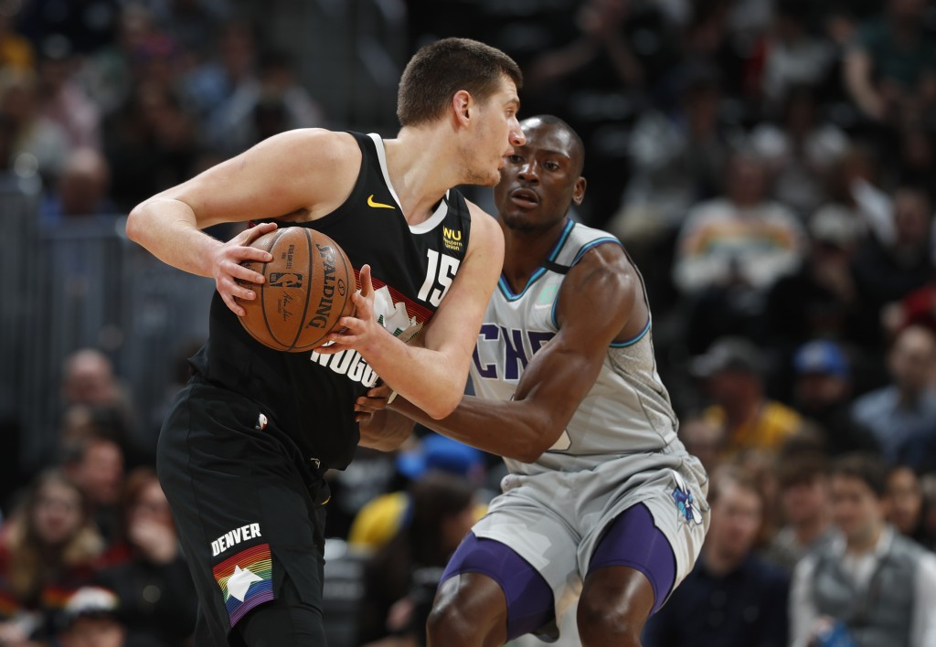 Denver Nuggets center Nikola Jokic, front, is defended by Charlotte Hornets center Bismack Biyombo during the first half of an NBA basketball game Wed...
