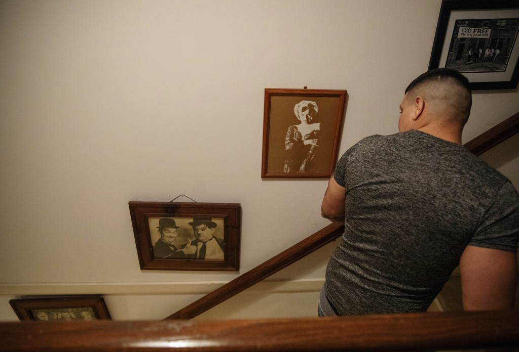 Yasnier Palacio Nieves, an asylum seeker from Cuba, walks past photos of Laurel and Hardy and Marilyn Monroe that hang on the wall of a local resident...