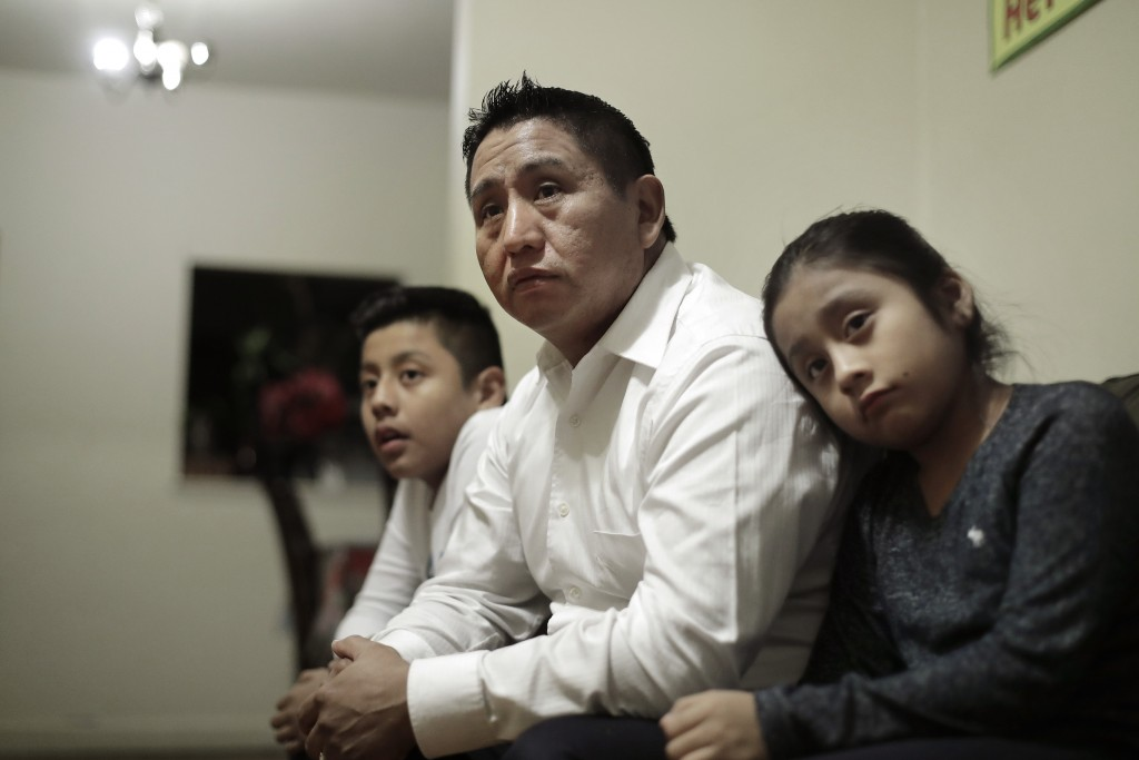 In this Nov. 21, 2019, photo Audencio Lopez, center, who crossed the border illegally as a teenager in 1997, is seated with two of his children, Anaia...