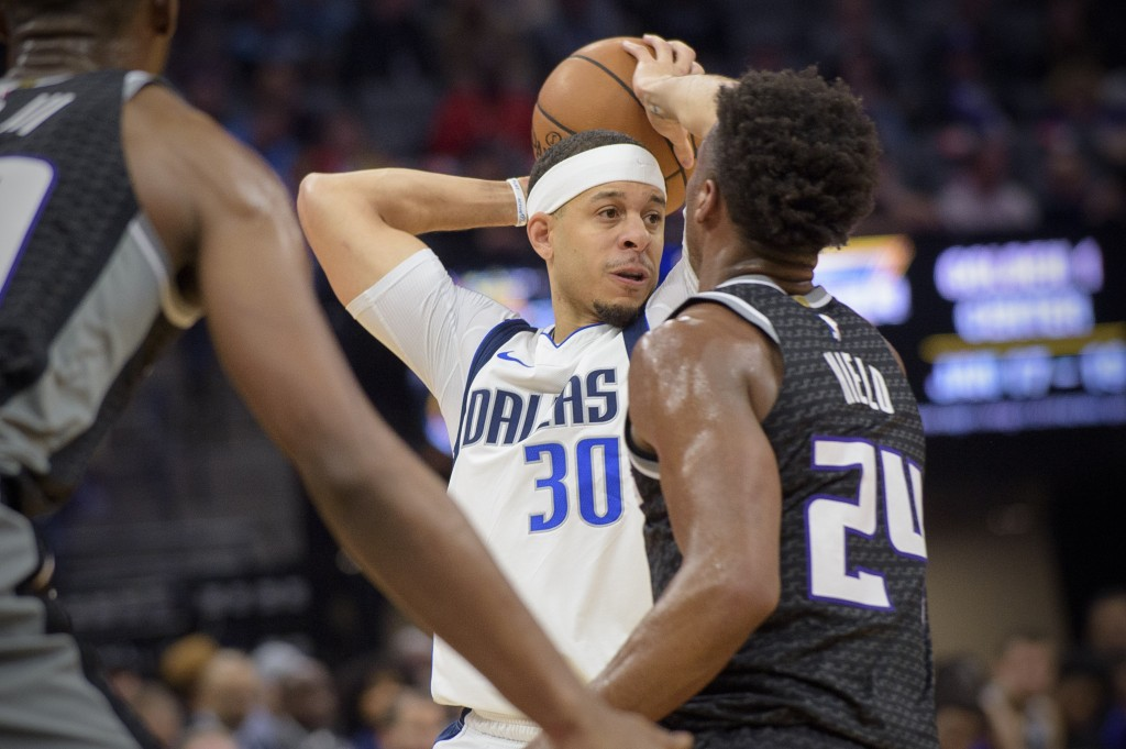 Dallas Mavericks guard Seth Curry (30) passes the ball over Sacramento Kings guard Buddy Hield (24) during the first quarter of an NBA basketball game...