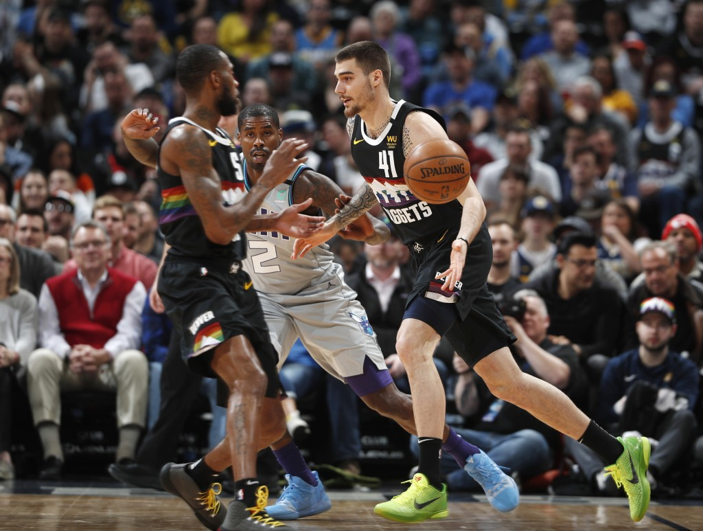 Denver Nuggets forward Juan Hernangomez, front, right, passes the ball to guard Will Barton, front left, as Charlotte Hornets forward Marvin Williams ...