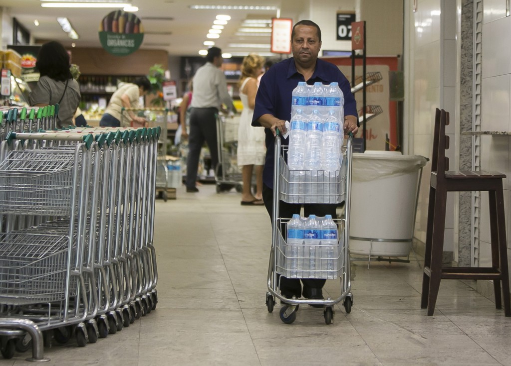 Almir Vicente pushes his recently bought bottled water at a supermarket in the Copacabana neighborhood of Rio de Janeiro, Brazil, Wednesday, Jan. 15, ...
