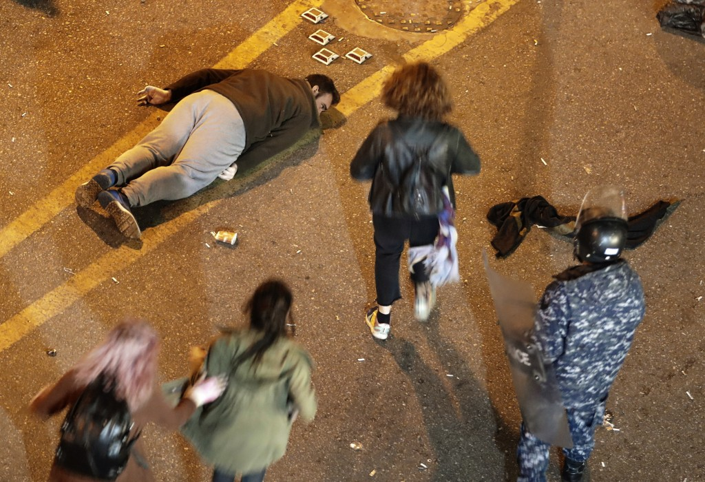 An anti-government protester lies on the ground after he was beaten by riot police, while he was was protesting outside a police headquarters demandin...