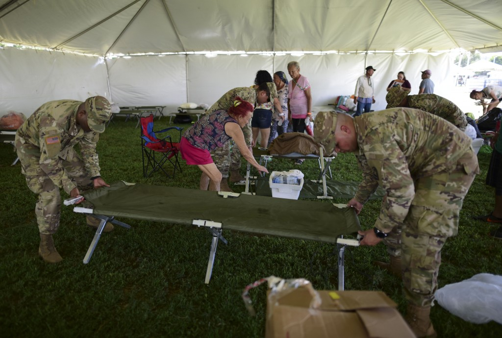 Members of the US army reserve assemble a cot as they set up a tent city to house hundreds of people displaced by earthquakes in Guanica, Puerto Rico,...