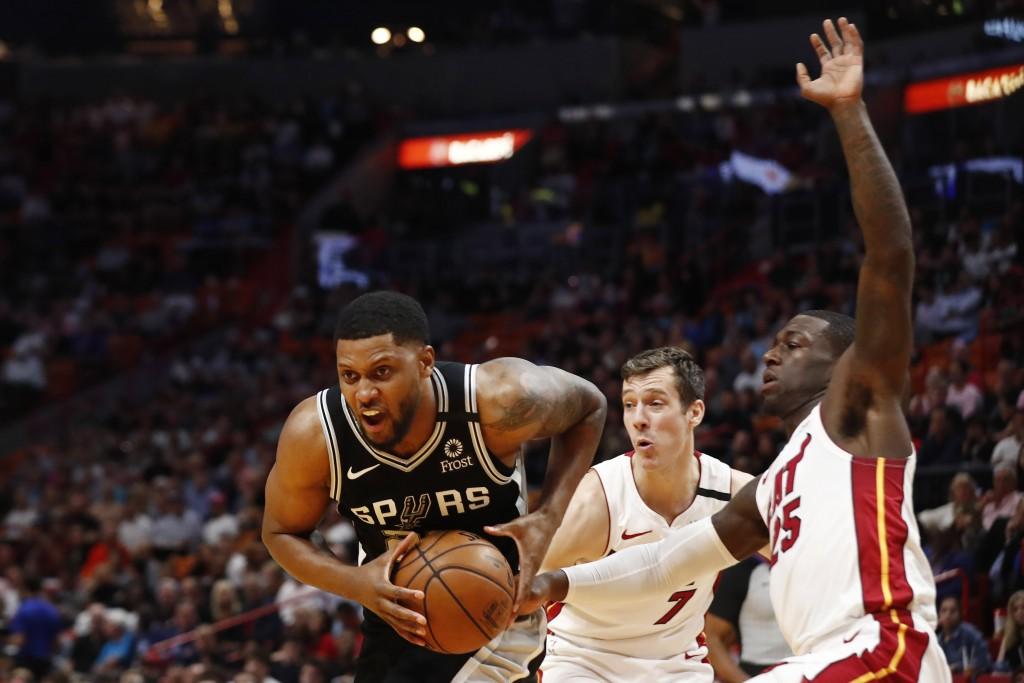 San Antonio Spurs forward Rudy Gay (22) holds the ball against Miami Heat guard Kendrick Nunn (25) and guard Goran Dragic (7) in the first half of an ...
