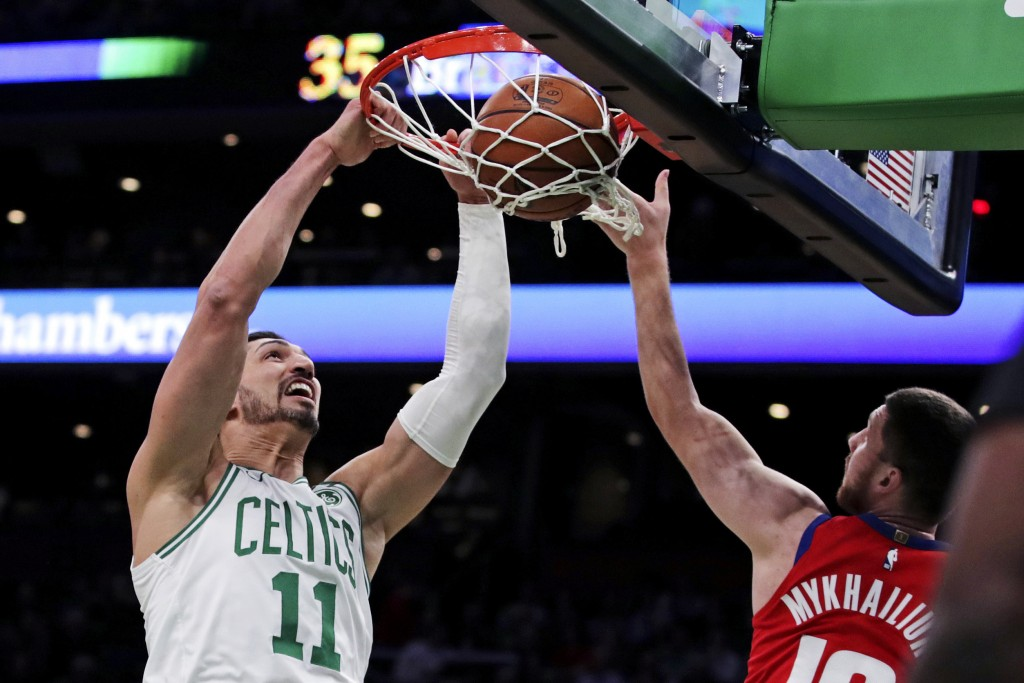 Boston Celtics center Enes Kanter (11) dunks next to Detroit Pistons guard Sviatoslav Mykhailiuk (19) during the first half of an NBA basketball game ...