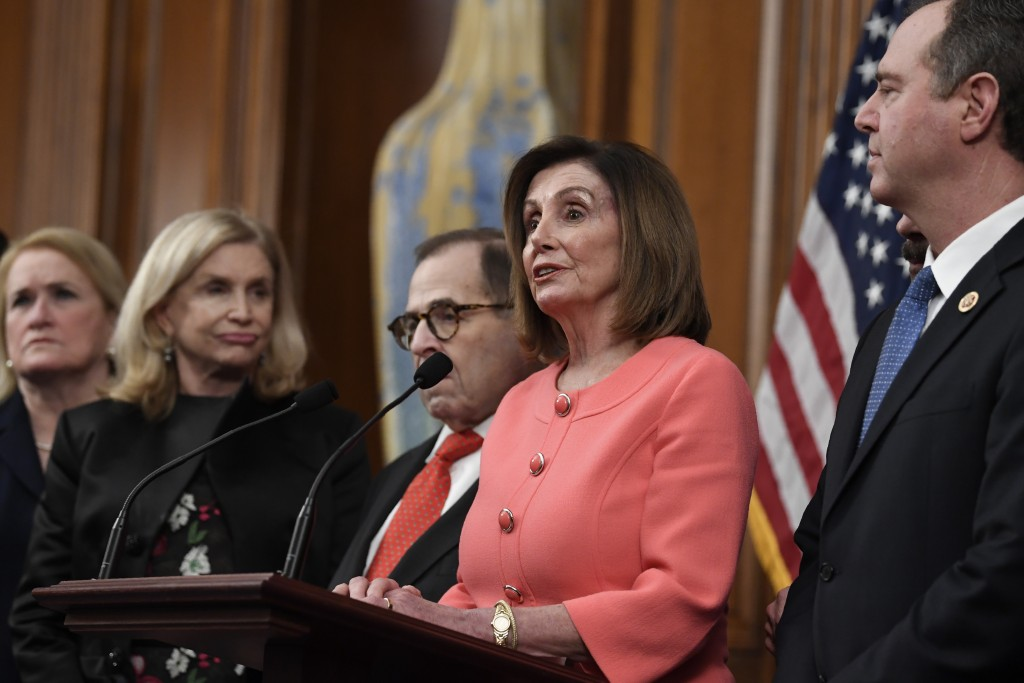 House Speaker Nancy Pelosi of Calif., second from right, speaks before signing the resolution to transmit the two articles of impeachment against Pres...