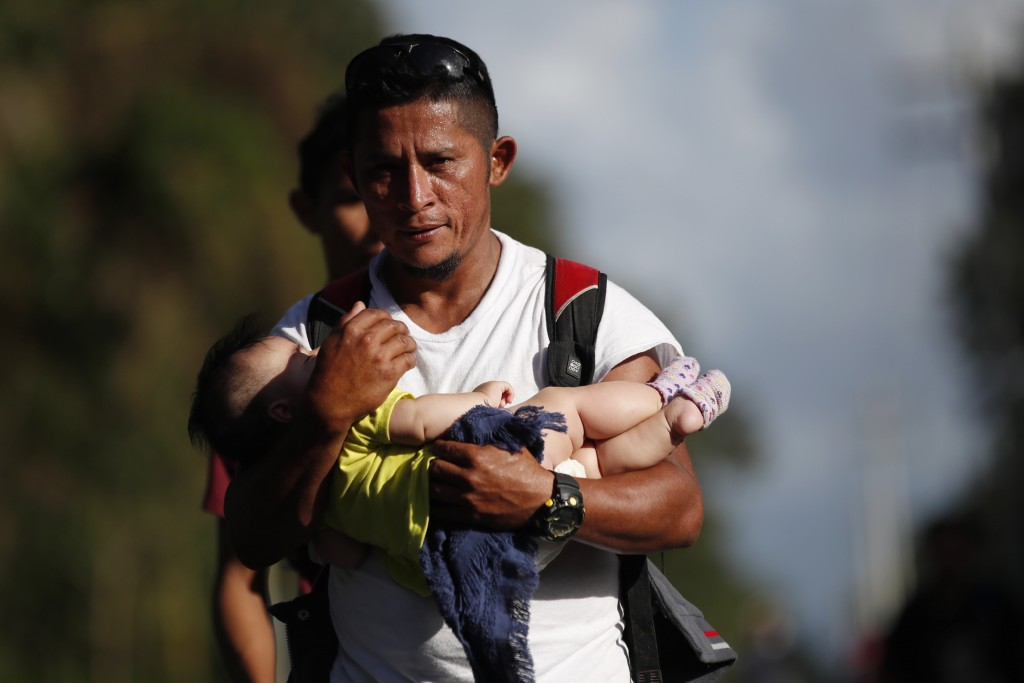 Honduran migrant Selvin Hernandez carries Mayra Irene, a daughter of another migrant, amid a group of migrants trying to make it to the United States,...