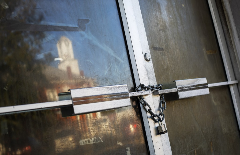 A shuttered storefront is padlocked as the Stewart County courthouse is reflected in the town square, Tuesday, Nov. 12, 2019, in Lumpkin, Ga. The town...