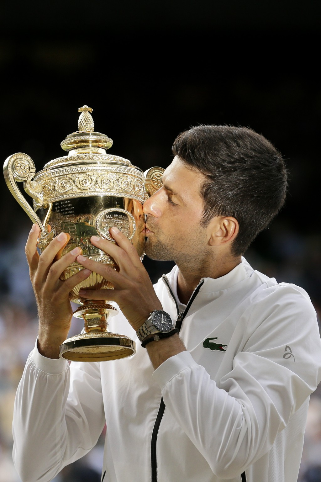 FILE - In this July 14, 2019, file photo, Serbia's Novak Djokovic kisses the trophy after defeating Switzerland's Roger Federer in the men's singles f...