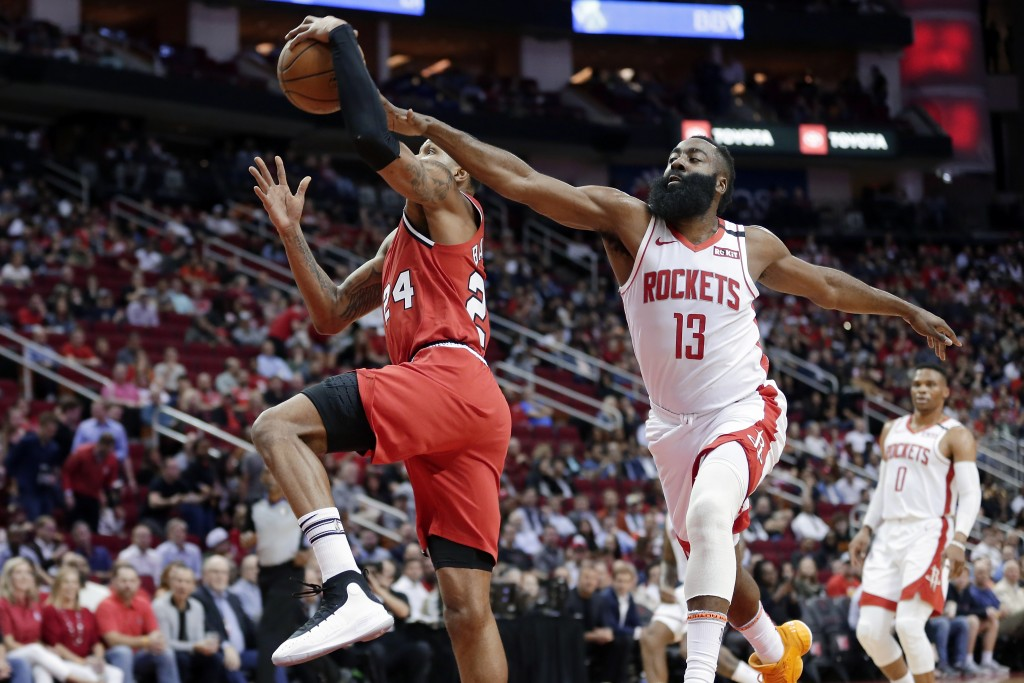 Portland Trail Blazers guard Kent Bazemore (24) is fouled on his shot attempt by Houston Rockets guard James Harden (13) during the first half of an N...