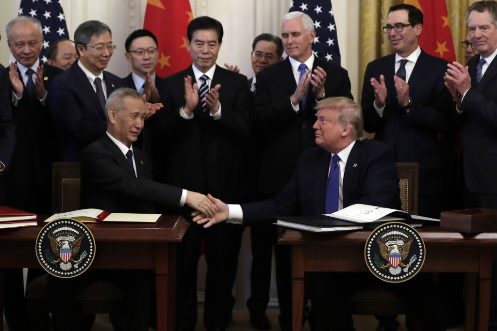 President Donald Trump shakes hands with Chinese Vice Premier Liu He, after signing a trade agreement in the East Room of the White House, Wednesday, ...