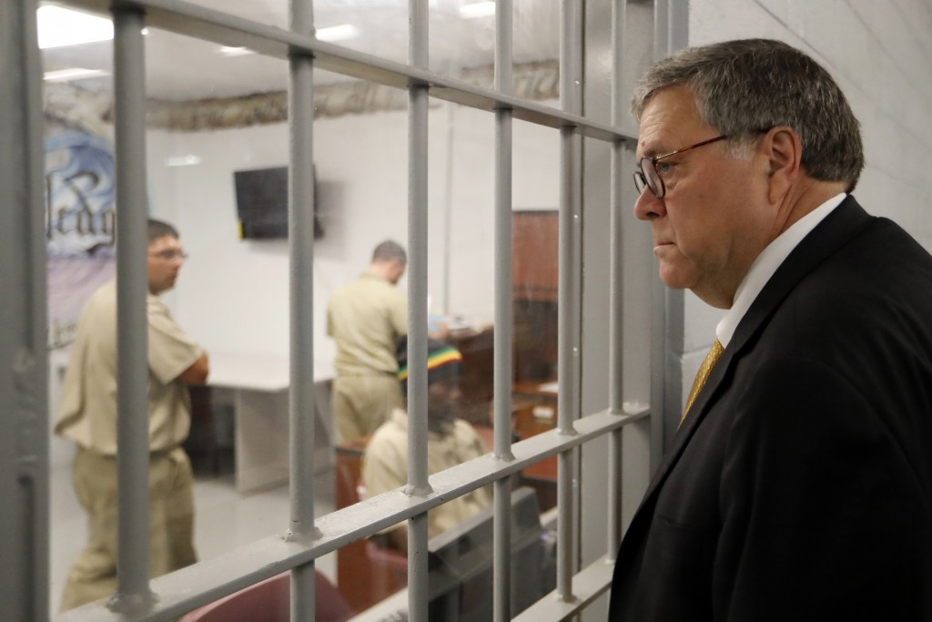 FILE - In this July 8, 2019, file photo, Attorney General William Barr watches as inmates work in a computer class during a tour of a federal prison. ...