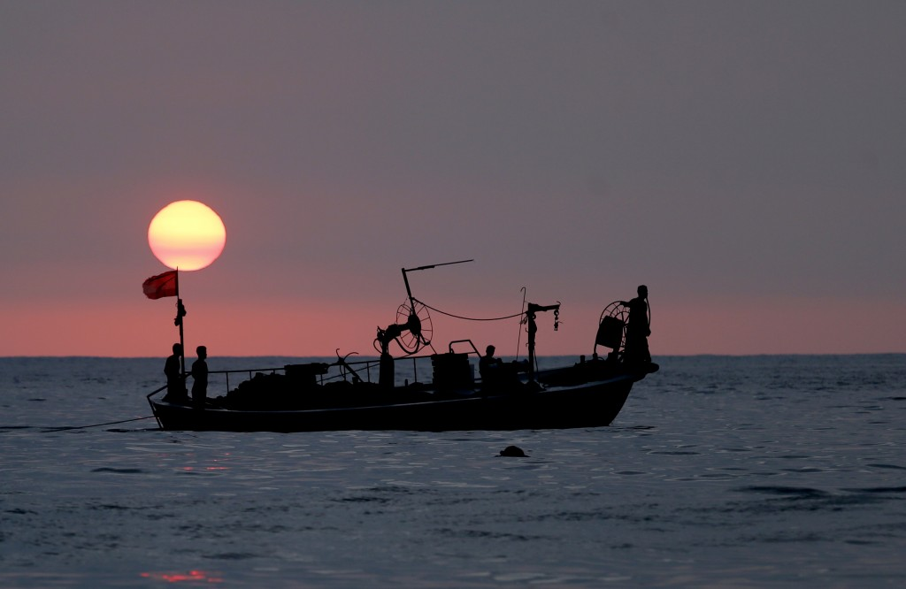In this Thursday, Aug. 30, 2018 file photo, Lebanese fishermen sit at the bow of a fishing boat, in the Mediterranean Sea as the sun sets, at Ramlet a...