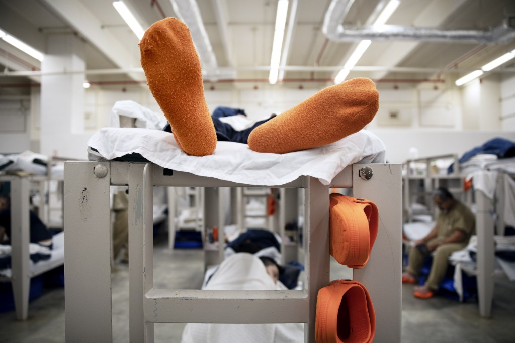 In this Friday, Nov. 15, 2019, photo, detainees lay on their bunks in their pod at the Stewart Detention Center, in Lumpkin, Ga. The rural town is abo...