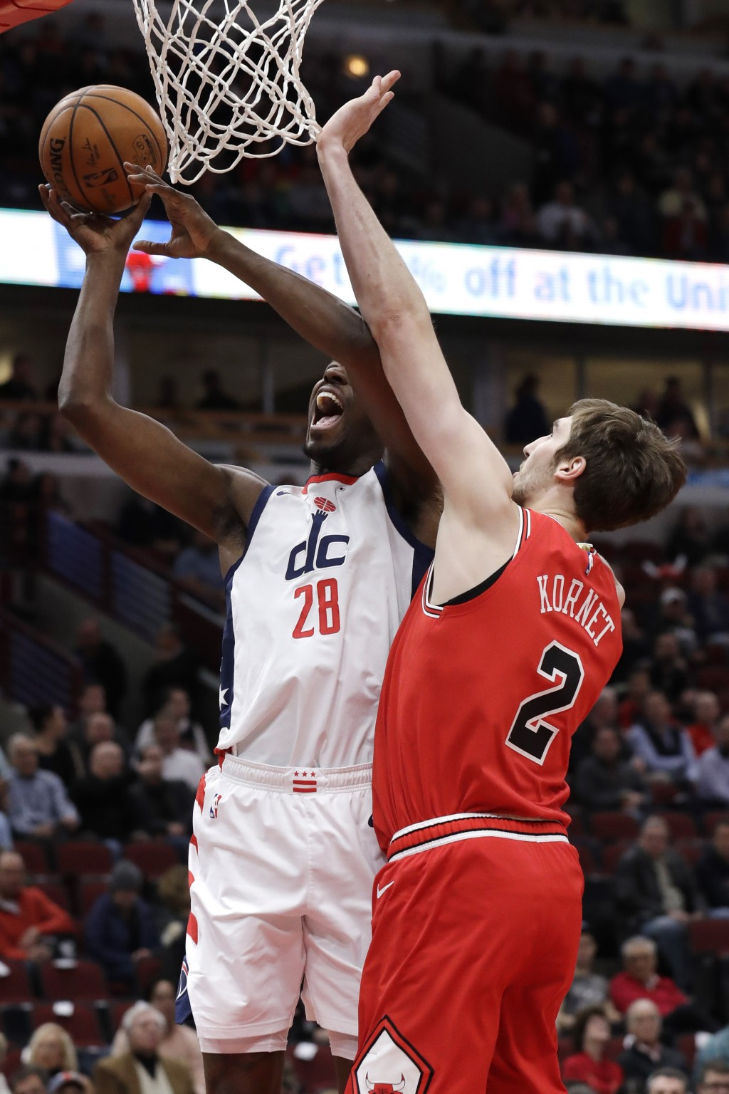 Washington Wizards center Ian Mahinmi, left, shoots next to Chicago Bulls forward Luke Kornet during the first half of an NBA basketball game in Chica...